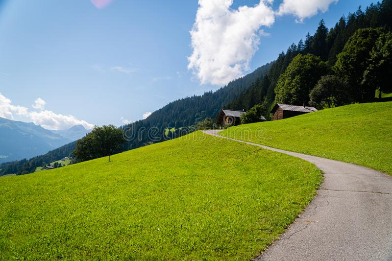 Narrow empty road winding by few mountain cottages with beautiful Montafon valley in Austria in background - Sunny summer day in stock photography