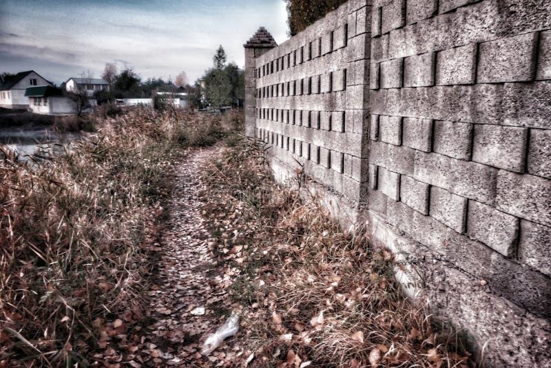 Narrow footpath through the dried grass next to the brick wall stock photos