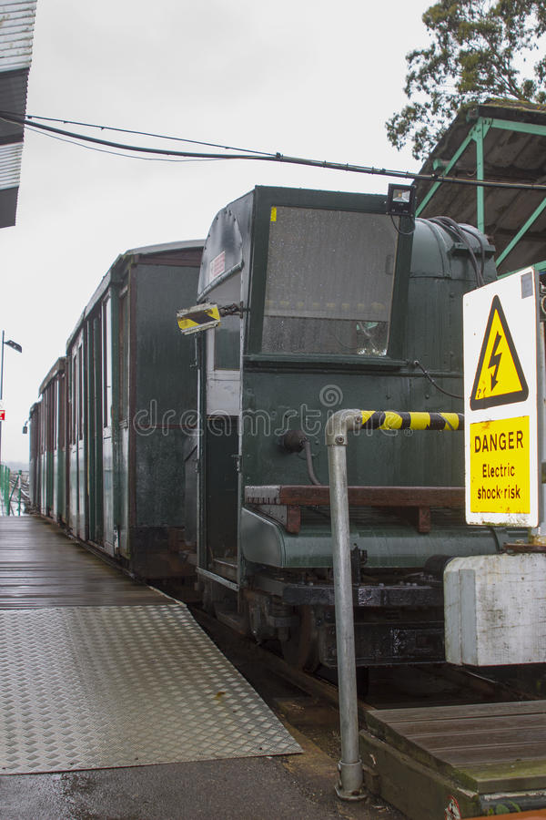 The narrow gauge train that runs the length of the Hythe Pier carrying passengers to and from the ferry boat to Southampton taken. On a dull wet summer`s day royalty free stock image