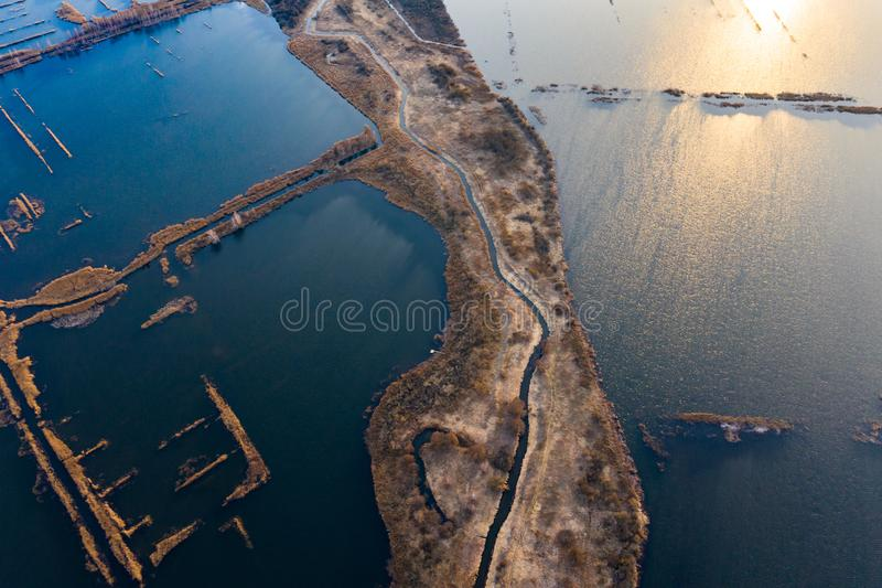 Narrow land edge surrounded by rippling waters, aerial landscape. Industry concept stock photography