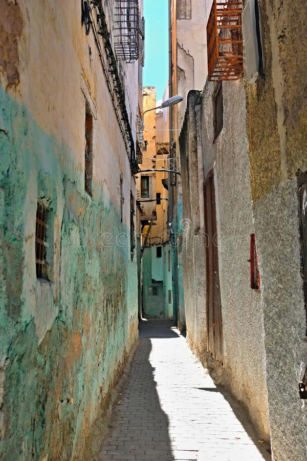 Narrow lane with walls of houses painted in different colors and in poor condition.  stock photography
