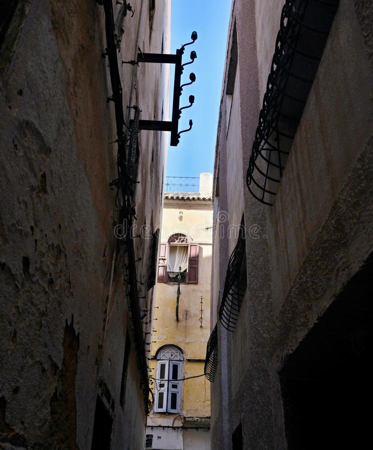 Narrow lane with walls of houses painted in different colors and in poor condition.  stock image