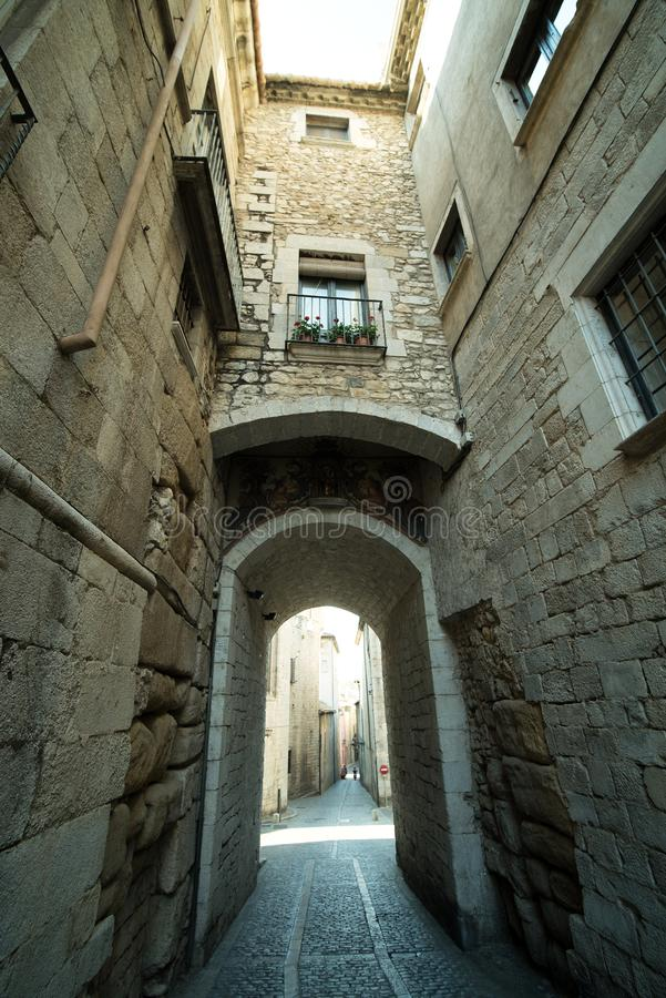 Narrow medieval street with arch in Girona city, Spain stock images