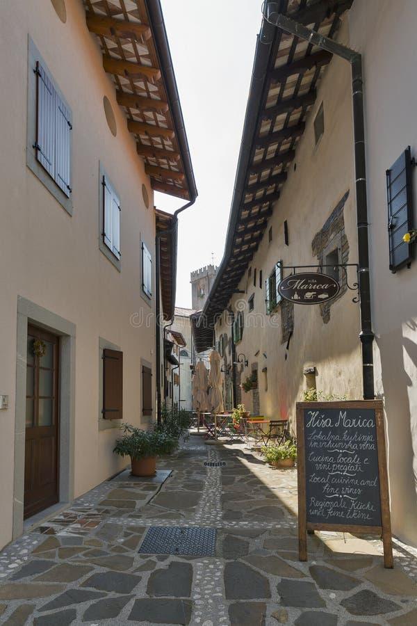 Narrow medieval street in Smartno village, Western Slovenia. Narrow medieval street with cafe and small hotel Marica. Smartno is a village in Brda region. The stock photography