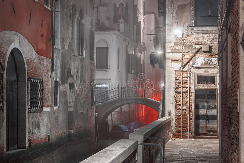 Narrow night street with a water channel in Venice stock photography