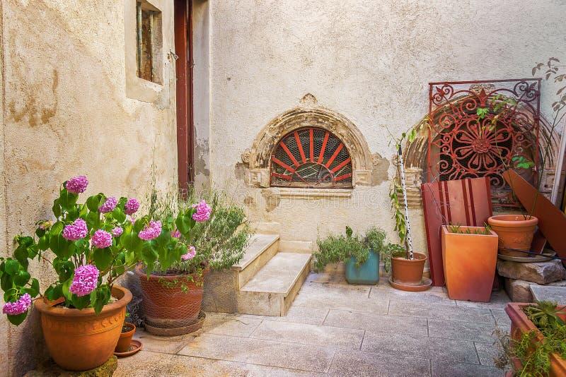 Narrow old street and yard in Sibenik city, Croatia, medieval zone royalty free stock image
