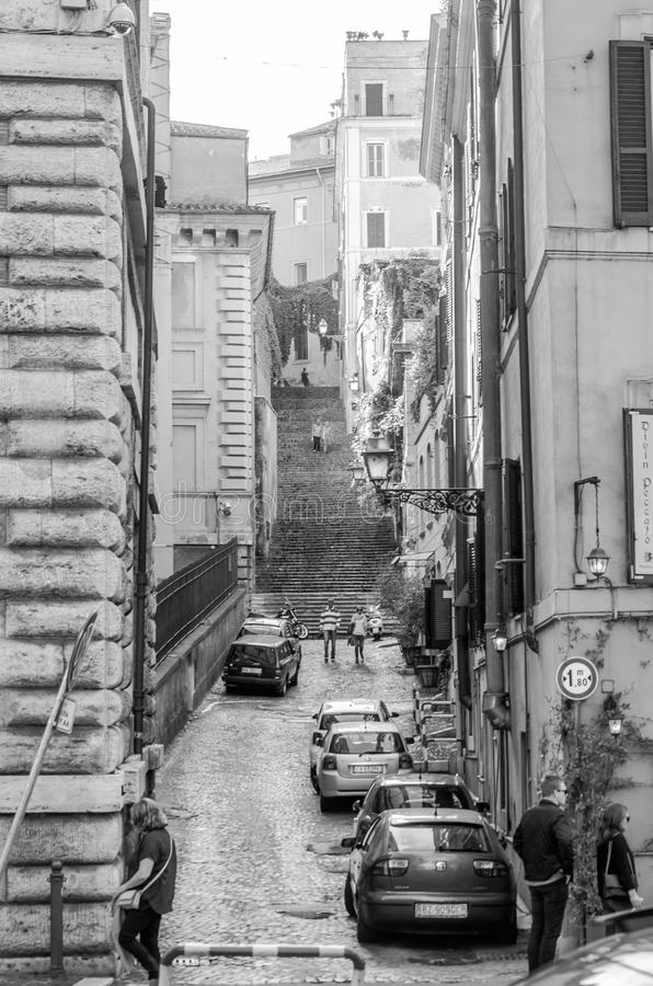 The narrow old streets of ancient Rome between the houses with stairs and tourists who walk through it considering attractions stock photos
