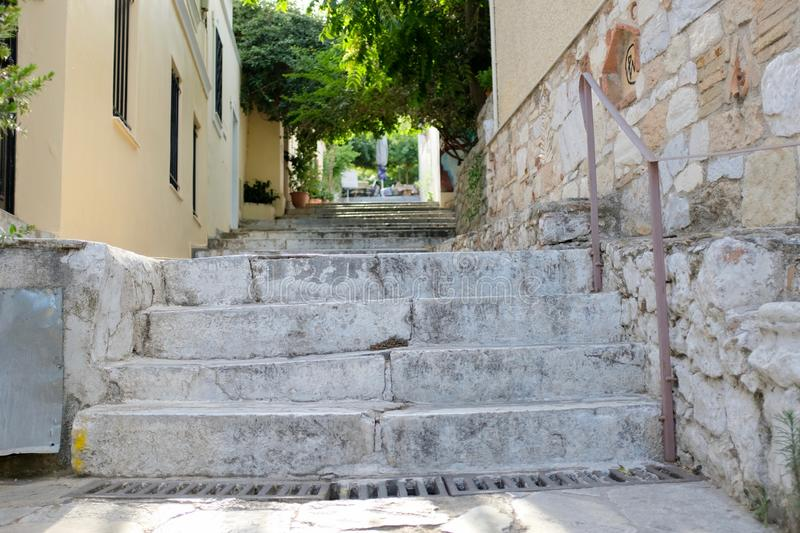 Narrow Passage and Marble Steps in Athens Alley. A typical narrow alley with stone sidewalk and walls, and marble steps in old town Plaka in Athens, Greece stock photography