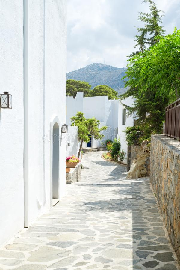 Narrow passage with white buildings and trees. From Greece stock photo