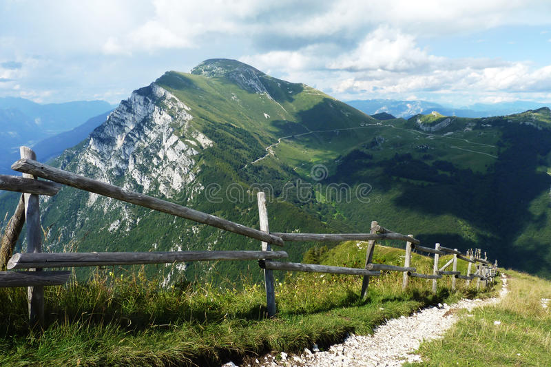 Narrow is the Path. A narrow path running along a fence on Monte Baldo in northern Italy. The Dolomites, part of the Italian Alps royalty free stock photos