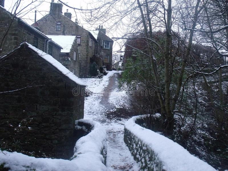 Footprints through the village in the snow. A narrow pathway leading over a stone bridge into the heart of the village royalty free stock photo