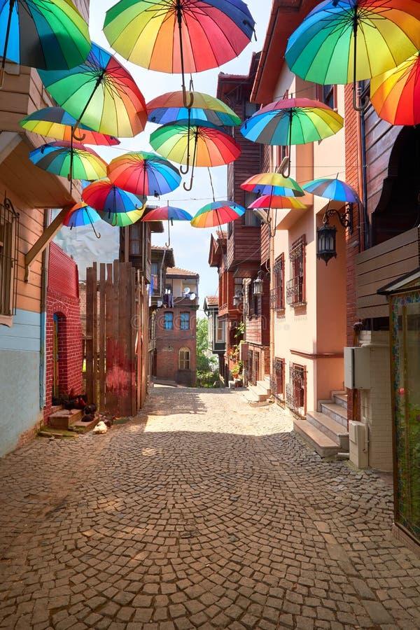 Narrow pedestrian street in Istanbul, Turkey, with rainbow umbrellas on display. Above the walkaway stock images