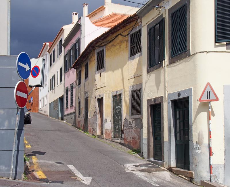 Narrow quiet empty street in funchal madeira with old painted houses on a steep hill with shutters and road signs. A narrow quiet empty street in funchal madeira royalty free stock photography