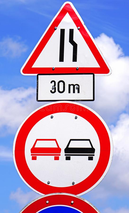 Narrow road and no overtaking traffic signs. In summer royalty free stock image