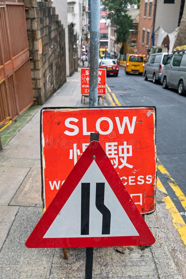 Narrow Slow Sign. Big Red Slow Traffic Sign Warning in City royalty free stock photography