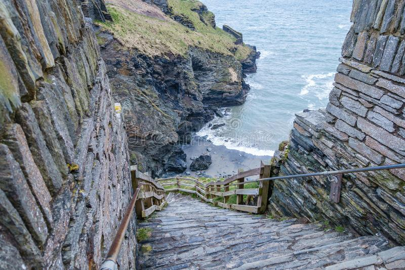 The narrow and steep steps down the cliff. Rocks by the sea, where only the grass grows; the narrow and steep steps down the cliff and along the edges are a stock photography