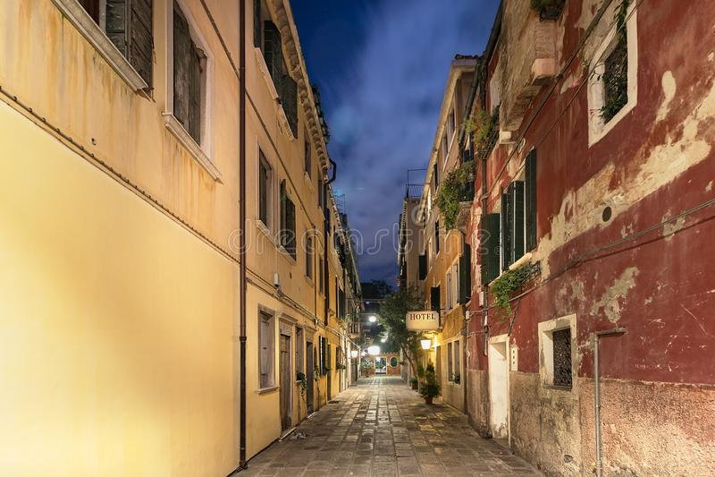 A narrow street with apartments and a hotel signboard iluminated at night, Venice, Italy royalty free stock image