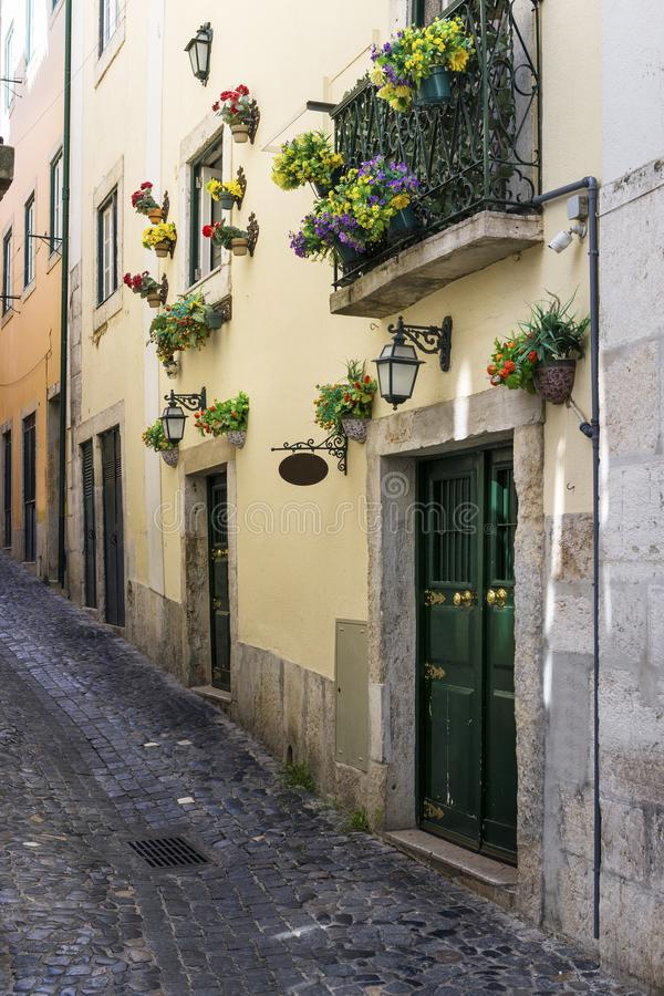 Narrow street and the facade of a building with flowers in the traditional neighborhood of Alfama in Lisbon, Portugal royalty free stock image