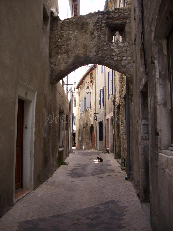 Narrow French street. Narrow street in a southern French town with arched links between buildings and a cat sat in the road stock images
