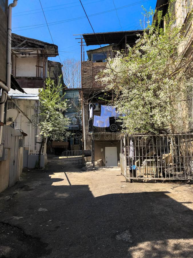 Narrow street, lane, tunnel with old houses, buildings on the sides in a poor area of the city, slums. Vertical photo royalty free stock images