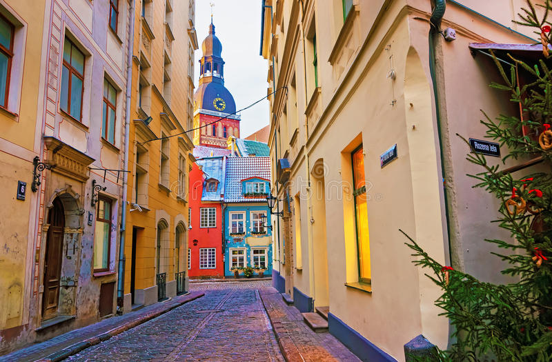 Narrow street leading to the St. Peter church in Old Riga stock photography