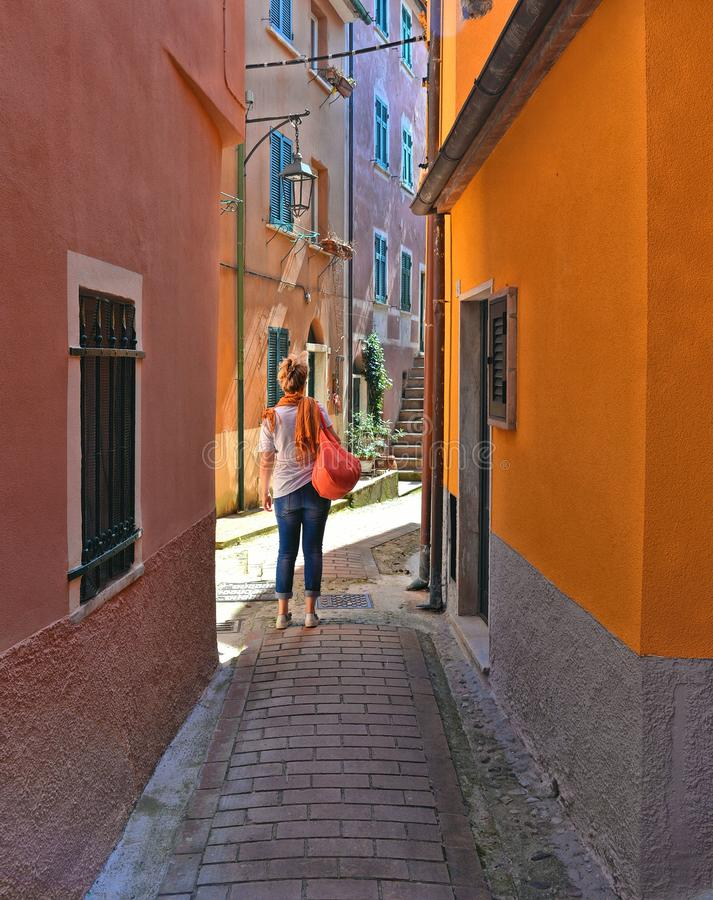 Narrow street with lonely person and colorful old buildings in old small village Montemarcello in Liguria, Italy. Woman royalty free stock photos