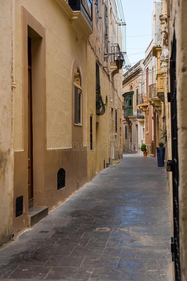 Narrow street in Mosta, Malta. Narrow Mediterranean alleyway in the medieval city of Mosta, Malta royalty free stock image