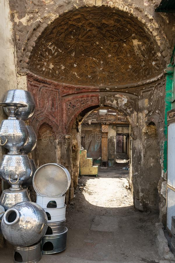 Narrow street with old building and traditional Egyptian aluminum vases, Old Cairo, Egypt. Arched passage between shabby houses with Egyptian traditional stock image