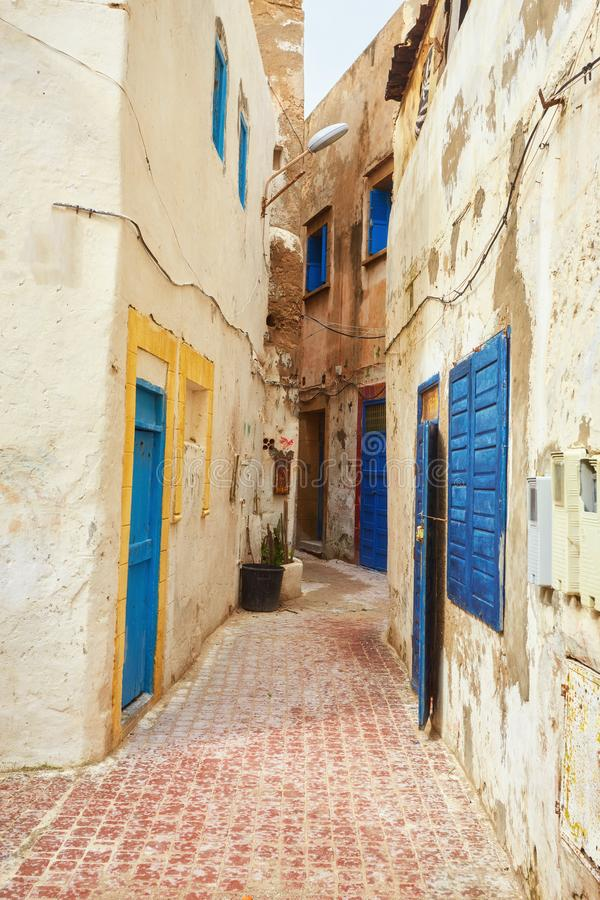 Narrow street of the old city with beige and white walls of the residential houses. royalty free stock photos