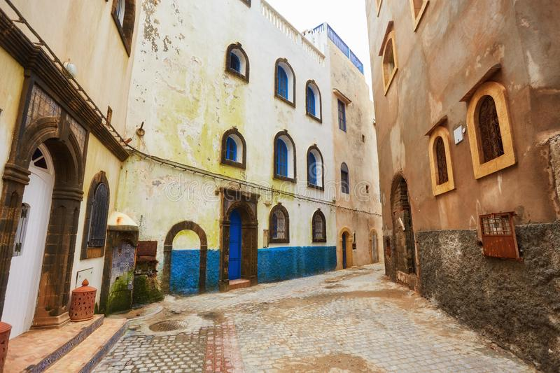 Narrow street of the old city with beige and white walls of the residential houses. royalty free stock images