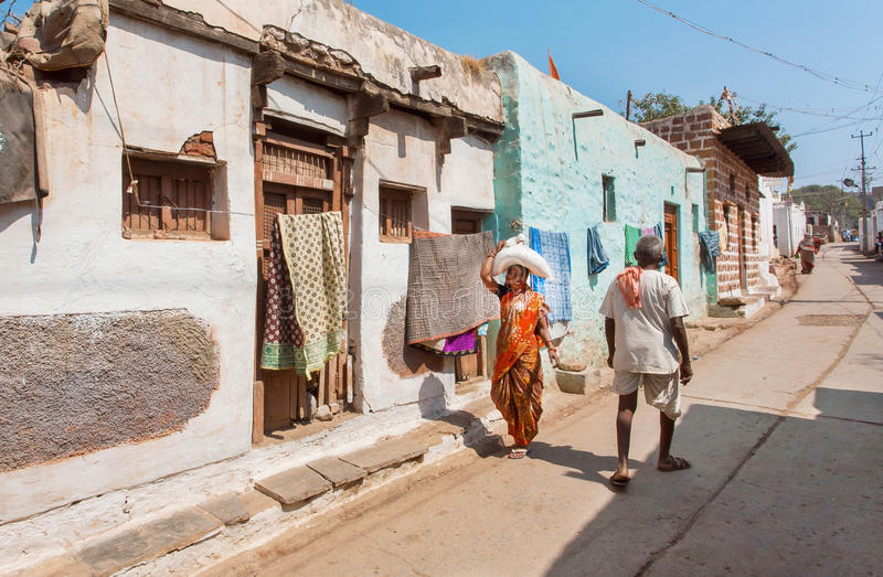 Narrow street of poor indian town with some people walking at hot day in Karnataka state royalty free stock images