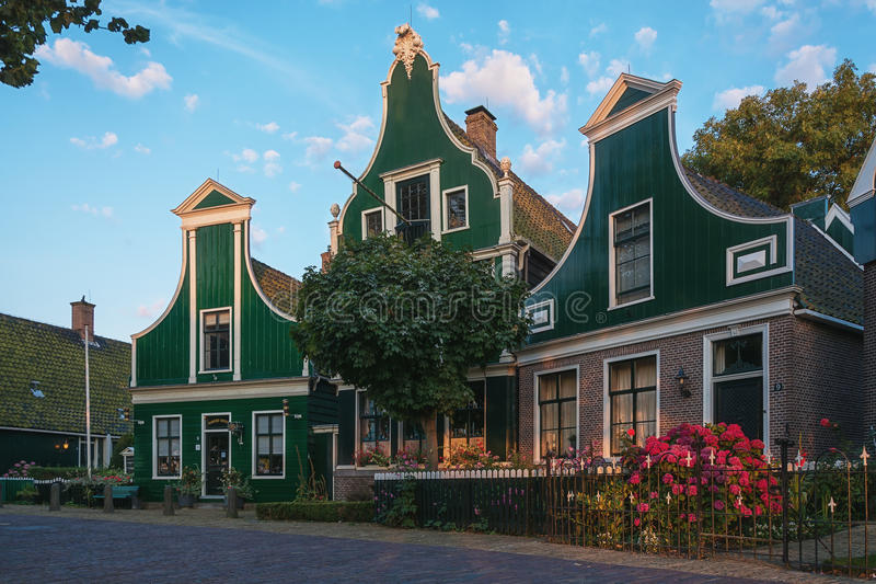 The narrow street in the small village of Zaanse Schans. Zaanstad, Netherlands, July 17, 2014: The Zaanse Schans with its windmills, typical green wooden houses stock photo