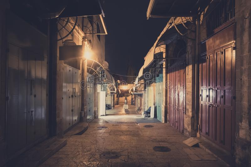 Narrow street of some middle east city at night time. Closed doors of the buildings along the deserted street footpath shot at royalty free stock images