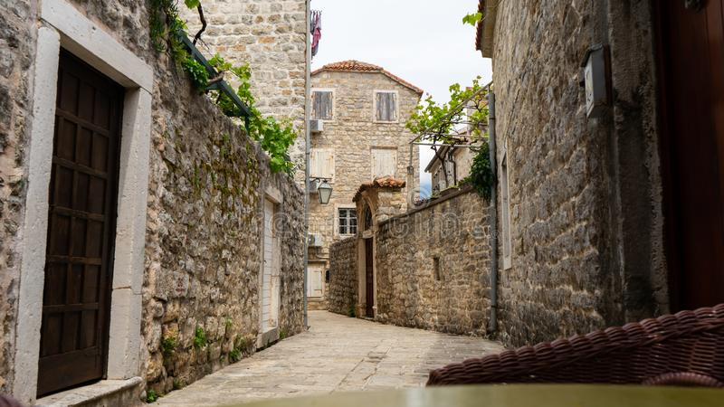 Narrow street with stone houses with vineyard. Budva citadel medieval town in Montenegro stock photo