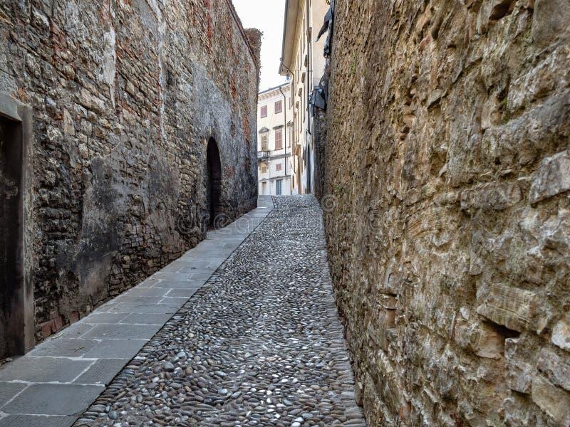 Narrow street between stone walls in Bergamo. Travel to Italy - narrow street Via S Salvatore with cobblestone pavement between stone walls in Upper Town (Citta royalty free stock image