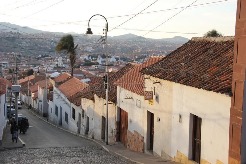 A Narrow street in Sucre. A narrow cobble stone street lined with white houses in going down a hill in the city of Sucre, Bolivia royalty free stock photography