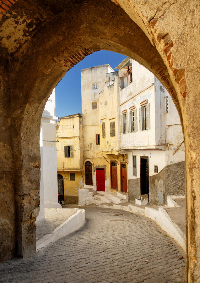 Narrow street in Tangier, Morocco. View to a narrow street through the city gate in Tangier, Morocco royalty free stock photos