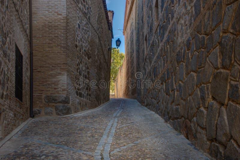 Narrow street of Toledo, Spain. Cobblestone narrow street leading to sunshine spot and blue sky royalty free stock photo