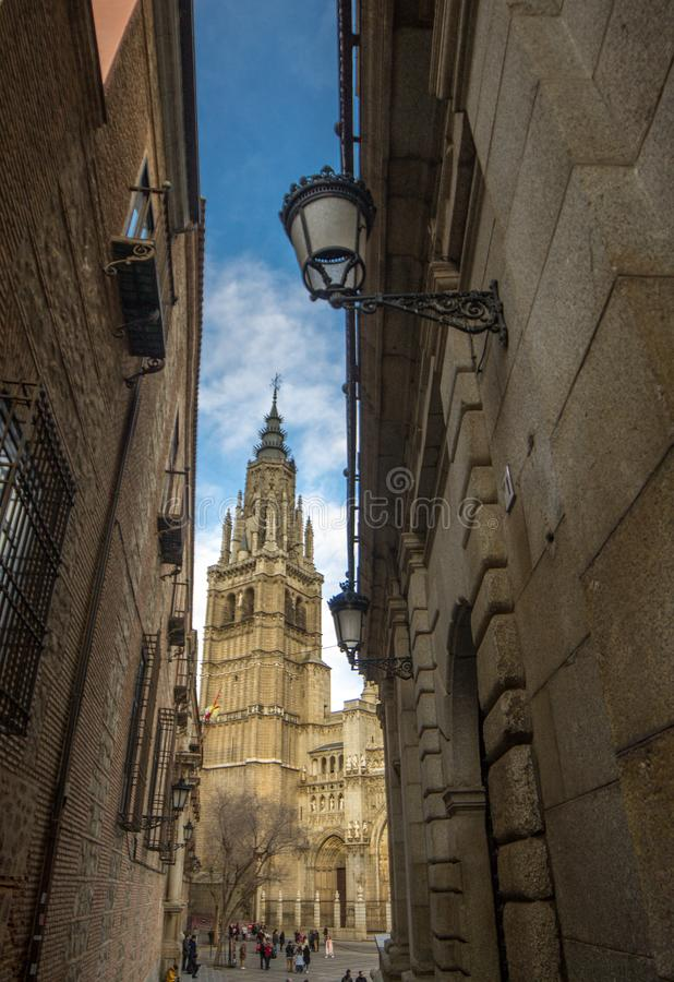 Narrow street of Toledo and tower of cathedral of Toledo royalty free stock image