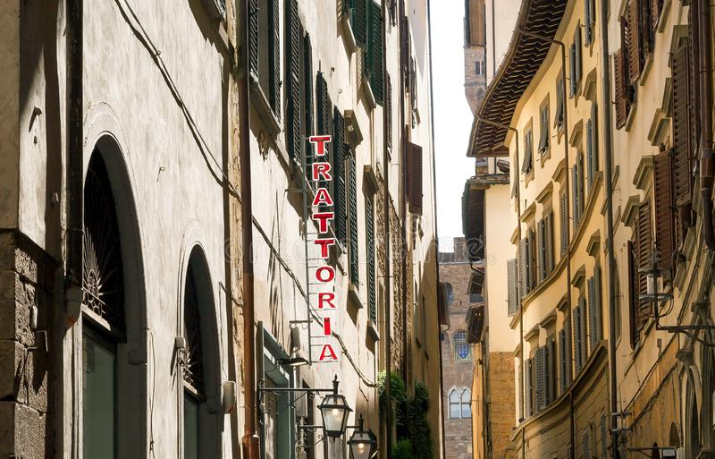 Narrow street with traditional italian trattoria, family restaurant sign. Healthy food place in Florence, Italy. Narrow street with traditional italian trattoria royalty free stock image