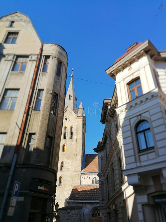 Narrow street between two buildings that leads to church, Cesis, Latvia royalty free stock image