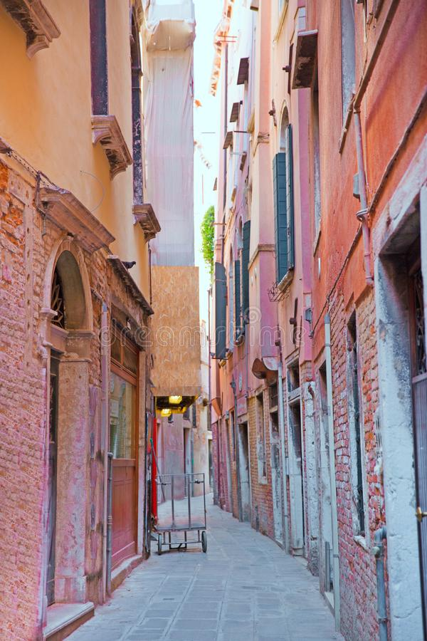 Narrow street in Venice, Italy. PInk and orange facades of old buildings. Beautiful narrow street in Venice, Italy. PInk and orange facades of old buildings stock images