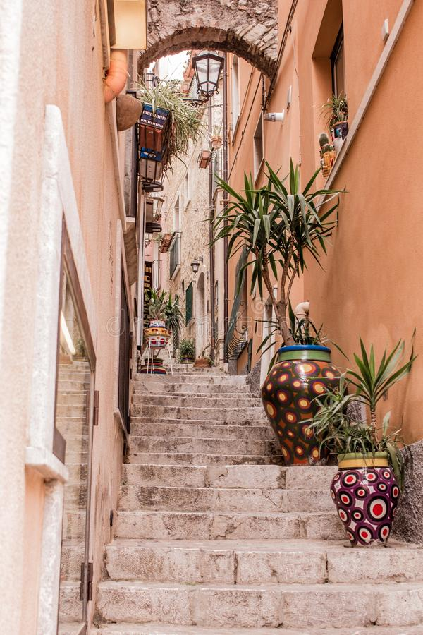 The narrow streets of the city of Taormina with its stores and medieval buildings on a sunny day. Sicily island, Italy. stock photos