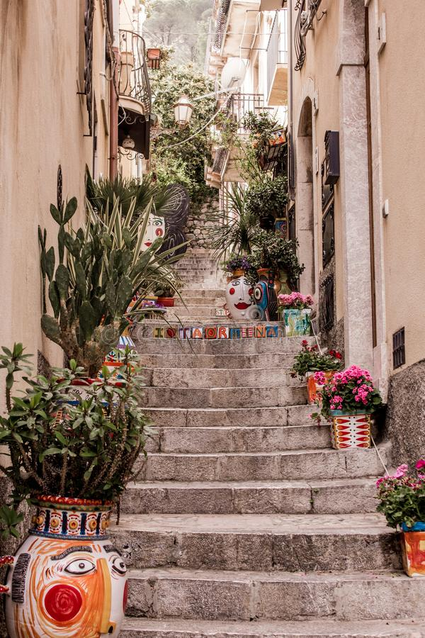 The narrow streets of the city of Taormina with its stores and medieval buildings on a sunny day. Sicily island, Italy. stock photo