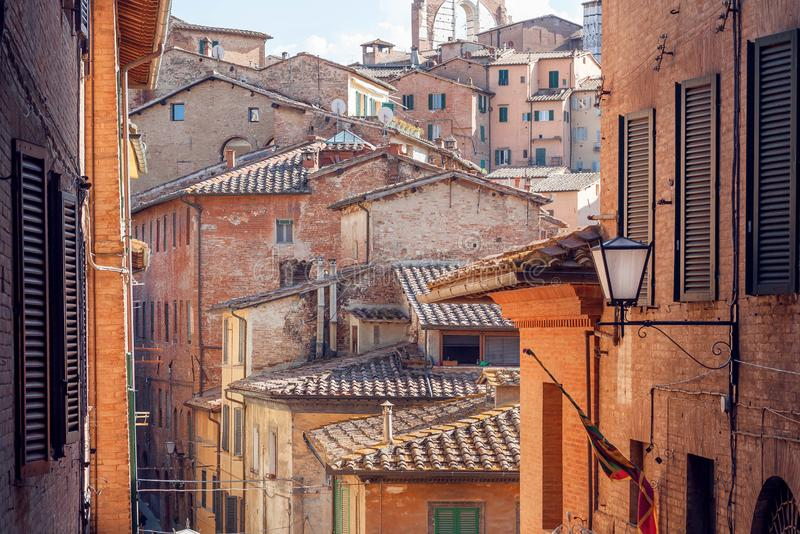 Narrow streets with historical houses of Siena, Tuscany. Tile roofs and brick structures in Italy. UNESCO Site. Narrow streets with historical houses of Siena stock photography