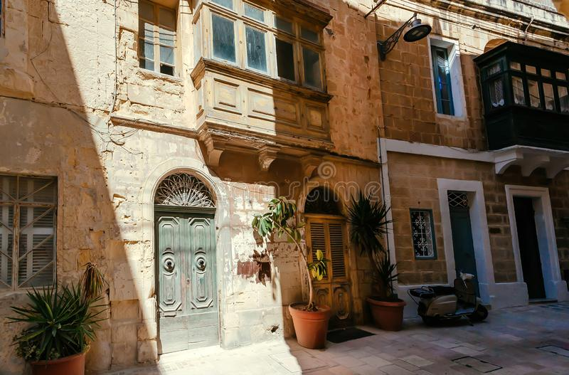 Narrow streets with wooden doors and historical stone houses of Malta royalty free stock photo
