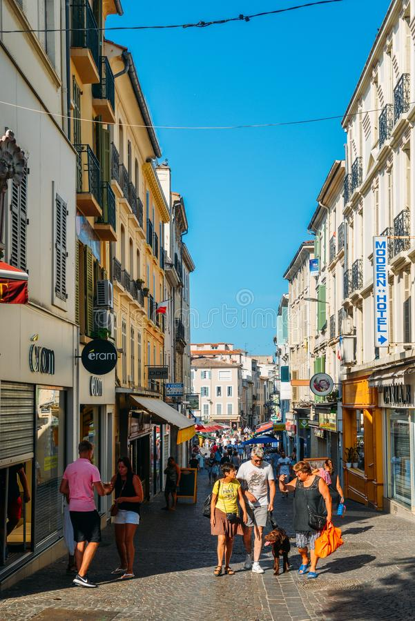 Narrow tourist street in Antibes, France. Antibes is a popular seaside town in the heart of the Cote d`Azur. Antibes, France - July 8, 2018: Narrow tourist stock image