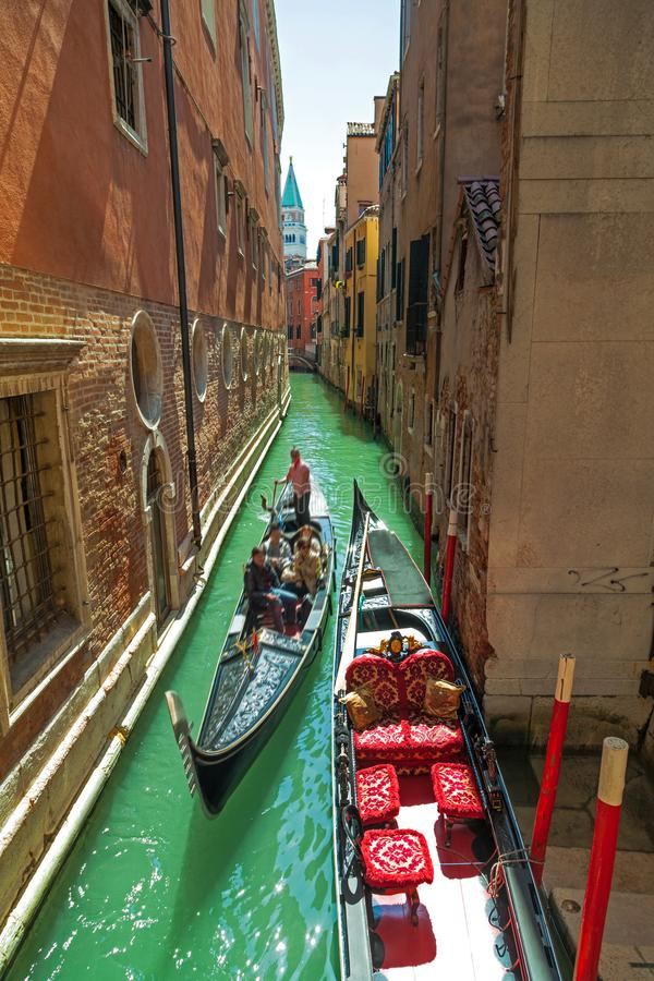 Narrow Venetian canal with gondolier and tourists in the gondola. stock image