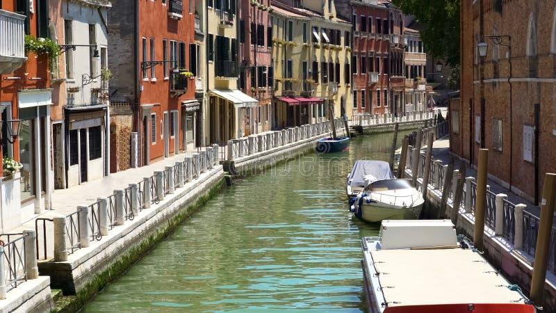 Narrow Venetian street, tourism and holidays, sunny days, boats on water royalty free stock photos