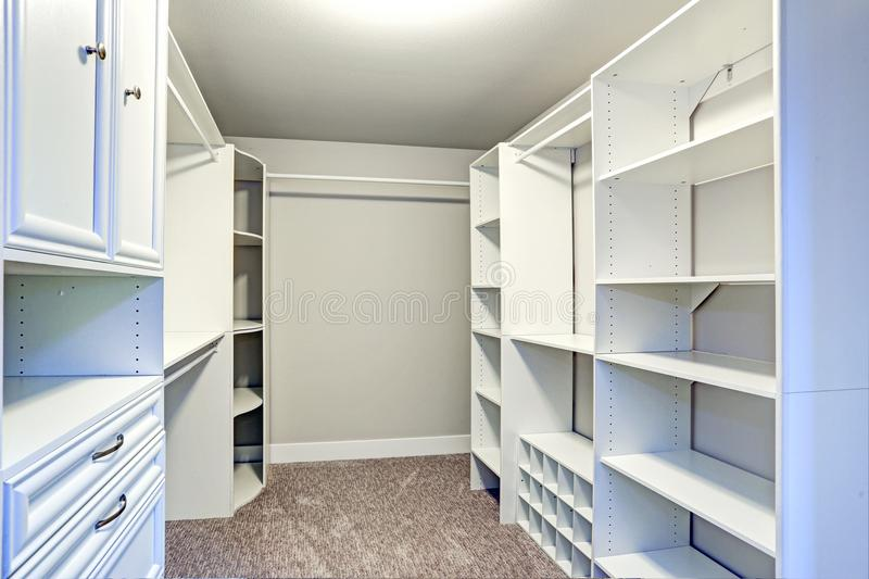 Narrow walk-in closet lined with built-in drawers royalty free stock images